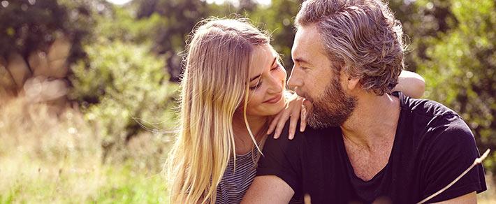 Paar mit großem Altersunterschied sitzt auf einer Wiese
