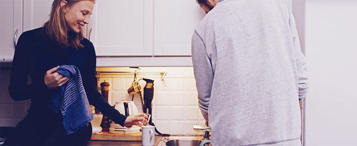 Ein Paar bei der Hausarbeit in der Küche – sie teilen sich die Aufgaben