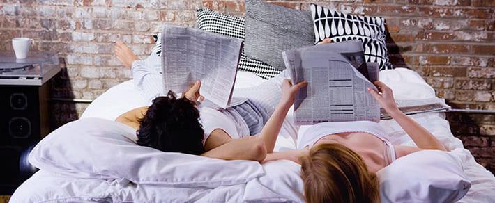 Ein Paar informiert sich morgens im Bett über die Bundestagswahl